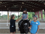 SI member, Renee McCabe Johnson and Equine-Assisted Therapies volunteer, Daniela present a ribbon to rider, Cassidy G.and horse, Sugar.