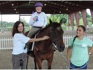 It's all smiles for SI Club Member, Susan Heimber, and volunteer Alina as rider, Katie R. and horse, Devon show off their ribbon.